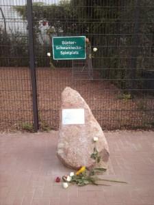 """Das Foto zeigt einen rötlichen, leicht nach links geneigten Findling, auf dem einen Gedenktafel für Günter Schwannecke angebracht ist. Dahinter ist ein grünes Schild zu sehen, auf dem mit weißer Schrift """"Günter-Schwannecke-Spielplatz"""" steht. Vor dem Findling liegen Blumen."""