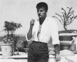 Auf dem Schwarzweiß-Foto ist Günter Schwannecke im Urlaub auf Ischia im Jahr 1958 zu sehen. Er ist damals etwa 25 Jahre alt. Er steht lässig auf einem Balkon zwischen zwei Topfpflanzen. Er trät eine dunkle Stoffhose, die bsi weit über die Hüften sitzt und ein weißes, offenes Hemd, das in die Hose gestekct ist. Mit der linken Hand stützt er sich auf ein Geländer auf, in der rechten Hand hält er eine Zigarette. Er hat einen Kurzhaarschnitt. Im Hintergrund ist eine Landschaft zu sehen.