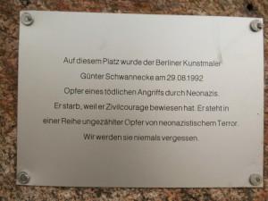 """Gedenktafel für Günter Schwannecke. Schwarz auf Blech eingraviert: """"Auf diesem Platz wurde der Berliner Kunstmaer Günter Schwannecke am 29.08.1992 Opfer eines tödlichen Angriffs durch Neonazis. Er starb, weil er Zivilcourage bewiesen hat. Er steht in einer Reihe ungezählterOpfer von neonazistischem Terror. Wir werden sie niemals vergessen."""" Im Hintergrund an den Rändern ist der rötliche Gedenkstein zu sehen."""