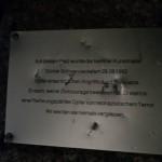 """Das Foto mit schlechter Lichtqualität wurde nachts aufgenommen. Es zeigt die metallische Gedenktafel, die auf den Günter-Schwannecke-Gedenkstein verschraubt ist. Zu sehen sind mehrere Löcher, Schrammen und Dellen, die mit einem Werkzeug in das Denkmal gerammt wurden. Zu lesen ist noch Aufschrift """"Auf diesem Platz wurde der Berliner Kunstmaler Günter Schwannecke am 29.08.1992 Opfer eines tödlichen Angriffs durch Neonazis. Er starb, weil er Zivilcourage bewiesen hatte. Er steht in einer Reihe ungezählter Opfer von neonazistischem Terror. Wir werden sie niemals vergessen."""""""