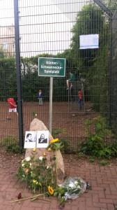 """Im Vordergrund mittig: Günter-Schwannecke-Denkmal ohne Gedenktafel (in Reparatur), stattdessen ein Foto von Günter Schwannecke und ein Selbstporträt von Hagen Knuth darauf geklebt. Davor am unteren Bildrand mittig: Blumen, die am Denkmal niedergelegt wurden. Im Hintergrund ist der Zaun des Spielplatzes zu sehen, auf dem Kinder spielen, davor ist in der Bildmitte das Ortsschild """"Günter-Schwannecke-Spielplatz"""" zu sehen. Oben rechts im Bild ist ein Aushang des Bezirksamts zu sehen, dass darauf hinweist, dass die Gedenktafel nach Beschädigung repariert wird."""