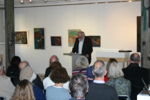Auf dem Foto ist zentral Walter Vitt zu sehen, wie er eine Rede zur Eröfffnung einer Ausstellung mit einer Kunstwerken von Rainer Plum und Günter Schwannecke hält. Im Vordergrund sind die Rücken der Gästinnen und Gäste der Ausstellung zu sehen. Im Hintergrund hängen Kunstgemälde.